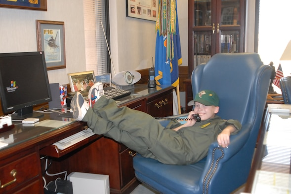 Pilot for a day, Nick McCluen, 7, relaxes in the office of Brig. Gen. Tom Jones, 56th Fighter Wing commander, when he visited Luke Sept. 14. Nick enjoyed a full day of activities at the 310th Fighter Squadron learning what it's like to be an F-16 pilot. (photo by 2nd Lt. Bryan Bouchard)