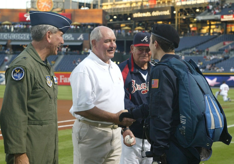 A parachutist from the Air Force Wings of Blue, Air Force Academy presents Brig. Gen. Ric Stevenson, Air Force Reserve vice commander, Georgia Governor Sonny Perdue and Bobby Cox, manager of the Atlanta Braves with a baseball that was flown around the world.