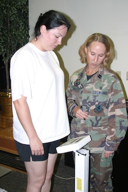 Tracy Stull (left) weighs in during registration for the second Biggest Loser contest as Capt. Beverly Thomas, 18th Aerospace Medicine Squadron officer-in-charge at the Health and Wellness Center, checks her weight. Progress will be tracked during monthly weigh-ins and the results will be e-mailed to all teams. (U.S. Air Force photo/Senior Airman Nestor Cruz)