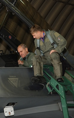 SPANGDAHLEM AIR BASE, Germany -- Capt. James Goeppinger, 23rd Fighter Squadron, helps Lt. Gen. Simeon Hristov Simeonov, Bulgarian air force commander, strap into this seat and explains the layout of the cockpit prior to their F-16 flight Sept. 19, 2007. General Simeonov traveled to Spangdahlem Air Base to for an orientation tour. (U.S. Air Force photo/Airman 1st Class Allen Pollard)