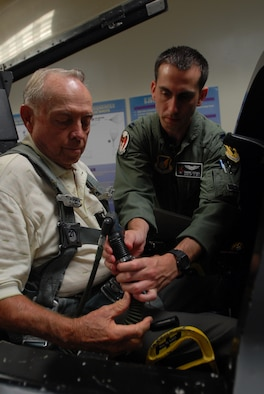 Capt. Ronen Segal shows how to attach the oxygen mask to Col. (ret.) and former Prisoner of War Jim Lamar in the emergency egress cockpit trainer during his egress training  at Kadnea Air Base, Japan, Sept. 20, 2007. Mr. Lamar was a POW during Vietnam and will be speaking at the base's POW/MIA ceremony Sept. 21.  After the ceremony, Mr. Lamar will receive an F-15C Eagle orientation flight. Captain Segal is a pilot with the 44th Fighter Squadron. (U.S. Air Force photo/Senior Airman Darnell T. Cannady)
