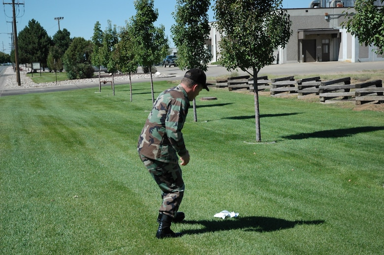 HILL AIR FORCE BASE, Utah-- Col. Scott Chambers, 75th Air Base Wing commander, literally pulls off the side of the road to pick up a piece of trash on the base.  The commander believes in creating a beautiful environment to work and live in. (U.S. Air Force photo by Capt. Genieve David)