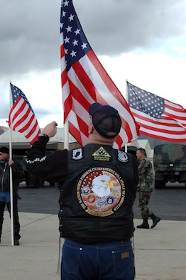 A member of the Patriot Guard Riders fixes his flag while waiting for the arrival of the 729th Air Control Squadron's aircraft to arrive on the flighline. The 729th ACS returned home after a four-month deployment to Balad Air Base, Iraq.