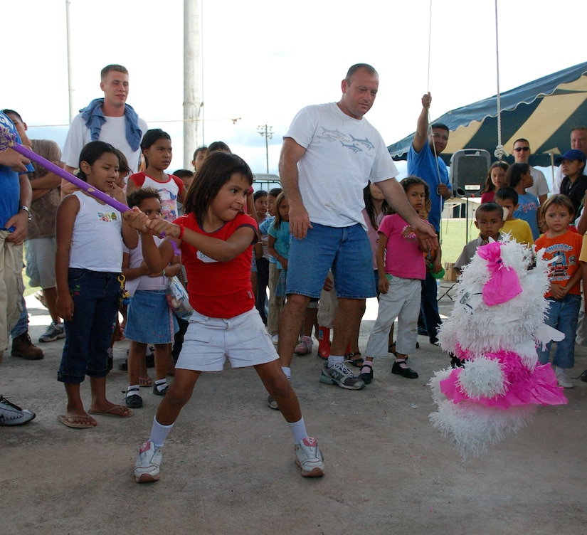 SOTO CANO AIR BASE, Honduras – A young Honduran girl winds up to deliver a crushing blow to a piñata while her friends cheer her on and wait anxiously for their turn to take a swing at it.  Approximately 90 children from Nuestra Señora de Guadalupe Children's Home in Comayagua came out to enjoy the Annual Kids Day celebration September 22.  (U.S. Air Force photo by Staff Sgt. Austin M. May)