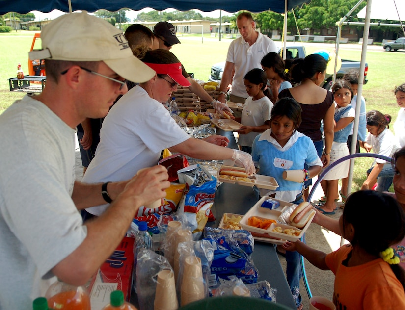 SOTO CANO AIR BASE, Honduras – Members of the United States Air Force cheerfully serve a hotdog lunch to Honduran children during a break in various games and activities.  Approximately 90 children from Nuestra Señora de Guadalupe Children's Home in Comayagua came out to enjoy the Annual Kids Day celebration September 22.  (U.S. Air Force photo by Staff Sgt. Austin M. May)