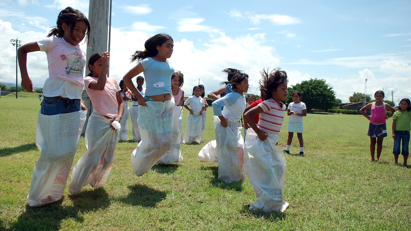 SOTO CANO AIR BASE, Honduras – As their friends enthusiastically cheer them on, a group of young Honduran girls race against each other in potato sacks.  Approximately 90 children from Nuestra Señora de Guadalupe Children's Home in Comayagua came out to enjoy the Annual Kids Day celebration September 22.  (U.S. Air Force photo by Staff Sgt. Austin M. May)