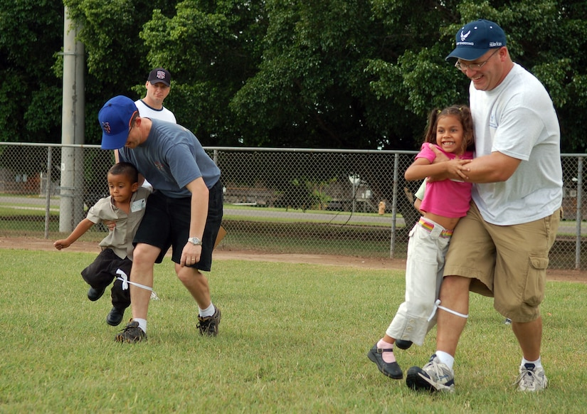 SOTO CANO AIR BASE, Honduras -- Air Force Tech. Sgt. David Johnson (front), airfield management, assists his Honduran partner in a three-legged race against Capt. Michael Epper, 612th Air Base Squadron, and his younger counterpart.  Approximately 90 children from Nuestra Señora de Guadalupe Children's Home in Comayagua came out to enjoy the Annual Kids Day celebration September 22.  (U.S. Air Force photo by Staff Sgt. Austin M. May)