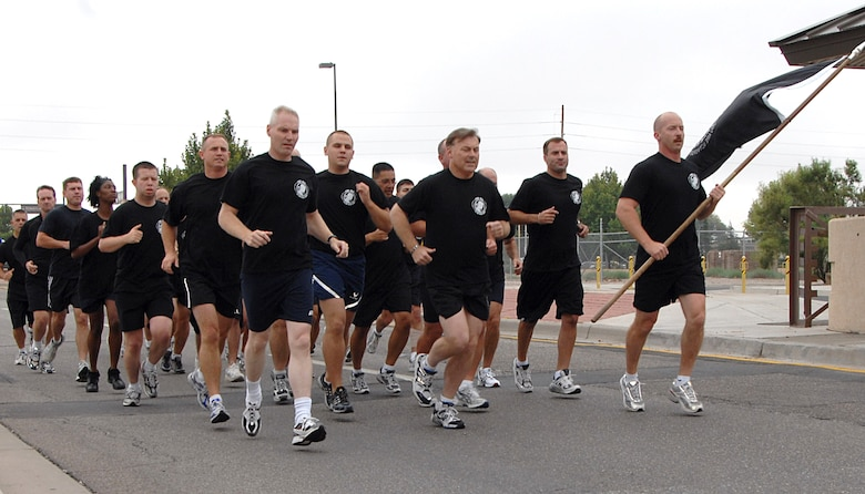 A formation of 5th Annual POW/MIA 24-Hour Vigil Runners from Kirtland AFB, N.M., led by Maj. Gen. Stephen T. Sargeant, Air Force Operational Test and Evaluation Center Commander (front middle) and Col. Matthew Bartlett, AFOTEC Vice Commander (front left), carry the POW/MIA flag from Kirtland's Hardin Field along a 1.5 mile course at the culmination of the run to deliver the flag to the off-base New Mexico Veterans Memorial on Sept. 21 for the combined POW/MIA Recognition Day ceremony sponsored by the Kirtland and Albuquerque communities.