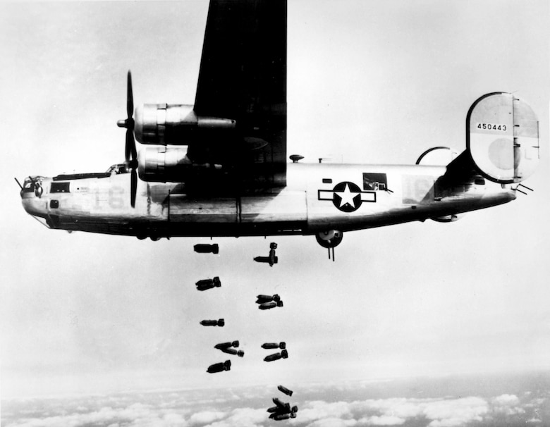 """World War II bomber crews faced the constant threat of enemy fighters and """"flak"""" during their missions over occupied Europe, much like the crew of this B-24 Liberator on a bombing mission over Germany in 1945.  Airmen faced capture by the German military when they were forced to parachute from damaged aircraft. (U.S. Air Force photo)"""