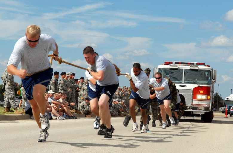 The 316th Training Squadron's Green Worms team pull a fire truck toward the finish during the Combined Federal Campaign Fire Truck Pull Tuesday. The Green Worms, who placed third with a time of 27.5 seconds, were among 25 teams which competed to support the CFC. (U.S. Air Force photo by Airman 1st Class Kamaile Chan)