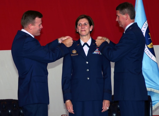 Col. Lori J. Robinson, commander of the 552nd Air Control Wing, receives her brigadier general stars pinned on by Brig. Gen. Tod Wolters (left), commander of the 325th Fighter Wing at Tyndall Air Force Base, Fla., and her husband, Maj. Gen. David Robinson, Mobilization Assistant to the Chief of the Air Force Reserves, during a brevet ceremony in Dock 2 on Sept. 21. (Photo by Senior Airman Lorraine Amaro)