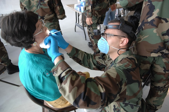 Captain Nicholas Marcus, 99th Dental Squadron, performs an oral cancer screening on Katsura Willson, retiree dependent, during the annual Nellis Retiree Appreciation Day, Sept. 22.  The event, held to recognize and honor military retirees, attracted approximately 800 prior servicemembers. (U.S. Air Force photo by Airman 1st Class Brian M. Ybarbo)