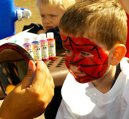 Tate Humphries, 3, closely inspects his Spiderman face painting at the Day for Kids Sept. 15 at the youth center. (U.S. Air Force photo by Karen Abeyasekere)