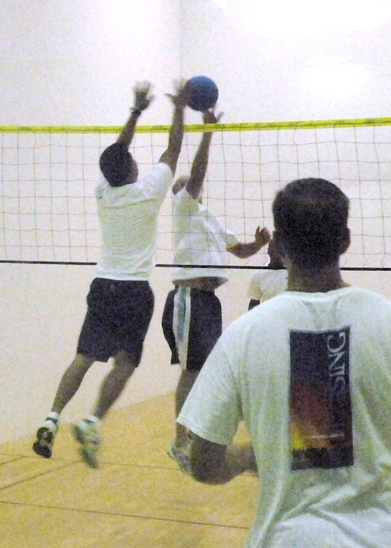 Col. Steve Beatty, 61st Air Base Wing vice commander and Master Sgt Rico Pamintuan, 61st Communications Squadron,  jump for the ball, while Chaplain Brad Kimble looks on during a walleyball game at the Los Angeles AFB Fitness Center, Sept. 19.  Played on a racquetball court, walleyball is similar to volleyball.  Sponsored by the Chaplain's Office, the base community is invited to join in the play every Wednesday from 7 to 8:30 a.m.  (Photo by Lou Hernandez)