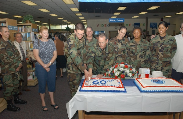 Col. Bob LaBrutta, 37th Mission Support Group commander, cuts a cake with Airman Basic Zachary Bruhn, 342nd Training Squadron, at the Lackland Base Library Sept. 17, 2007. The cake-cutting ceremony officially ended the week of festivities held in honor of the service's birthday. (USAF photo by Alan Boedeker)