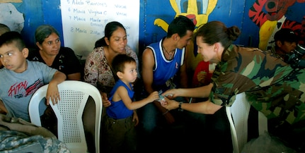 SAN JUAN OPICO, El Salvador – Air Force Tech. Sgt. Angel Roush, Joint Task Force-Bravo Medical Element, hands a bag of vitamins to a young Salvadoran boy at a makeshift clinic where doctors, nurses and medics from the United States and Salvadoran militaries conducted a Medical Readiness Training Exercise Sept. 27.  (U.S. Air Force photo by Staff Sgt. Austin M. May)