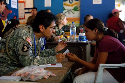 SAN JUAN OPICO, El Salvador – Army Capt. Marta Artiga, Joint Task Force-Bravo Medical Element, explains multivitamin dosage directions to Gabriela Alejandra, 13, at a makeshift clinic where doctors, nurses and medics from the United States and Salvadoran militaries conducted a Medical Readiness Training Exercise Sept. 27.  (U.S. Air Force photo by Staff Sgt. Austin M. May)