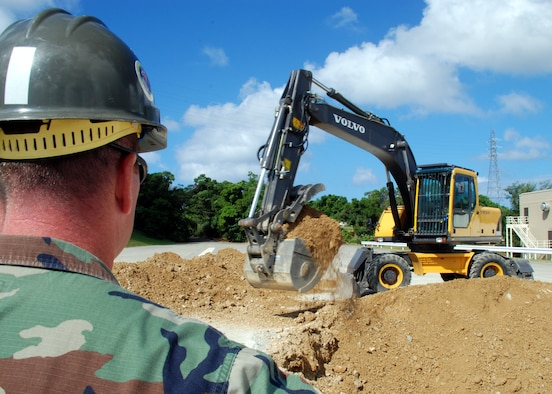 Equipment Operator 1st Class (SCW) David Martin supervises Equipment Operator 1st Class (SCW) Van Johnson as he excavates a crater September 25, 2007 in a simulated runway on Kadena Air Base as part of a joint-training exercise with the U.S. Air Force. 87 Naval Mobile Construction Battalion (NMCB) 7 personnel experienced the Rapid Runway Repair (RRR) training led by Kadena airmen to teach Seabees critical skills for their next deployment. NMCB 7 is currently deployed to the Far East to provide construction support to shore installations in support of the global war on terrorism.  (U.S. Navy photo/Mass Communication Specialist 2nd Class Michael B. Lavender )