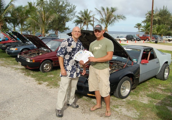 Second Lieutenant Marc Morin, 36th Services Squadron, presents Boonie Car Contest winner, Airman 1st Class John Lamb, 36th Civil Engineer Squadron, with $500 Services bucks towards fixing his vehicle at the Auto Hobby Shop.  Airman Lamb's 1986 Chevy Camaro took the prize as his exhaust system spouted puffs of black smoke when started; the quarter panel was on the verge of coming off; the lights were falling out of place; the seats were crooked; and the outside was painted in four different shades. (U.S. Air Force photo/Senior Airman Angelique Smythe)