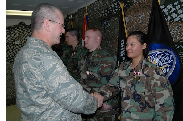 Brig. Gen. Craig McCord, JFMO Director of Joint Staff, congratulates Senior Airman Rita Wiley on her successful deployment to Afghanistan.
