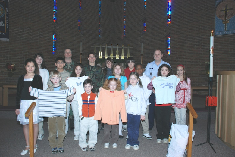 A group of Holy Ghost students present 107th ARW members with some of the clothes they collected for children in Iraq who are in need on March 26.  The clothes will be sent to Iraq where deployed members of the 107th security forces will distribute them to the children. Front row from left: Alyssa, Ben, Luke Wish, Amanda, Ellen.  Second row from left:  Alicia, Vishel, Lexi, Stephanie, Keonte, Jessica.Back row from left: Tech. Sgt. Chris Zastrow, Lt. Col. Deanna Miller, Sharleen, Stephen, Master Sgt. Bryan Lange.(US Air Force photo by Staff Sgt. Rebecca Kenyon)
