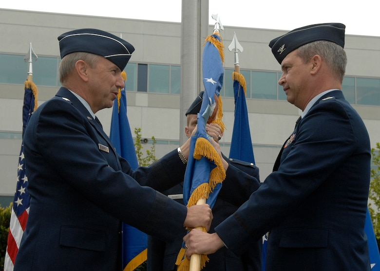 SMC Commander Lt. Gen. Michael Hamel passes the guide-on to Col. Christopher Pelc during a ceremony that marked the activation of SMC's Missile Defense Systems Group, April 1. Col. Pelc accepted the flag and assumes the title as the Group's Director. He will be responsible for activities associated with program execution of the Space Tracking and Surveillance System research and development program, Near Field Infrared Experiment and Advanced Technology Risk Reduction effort. (Photo by Stephen Schester)
