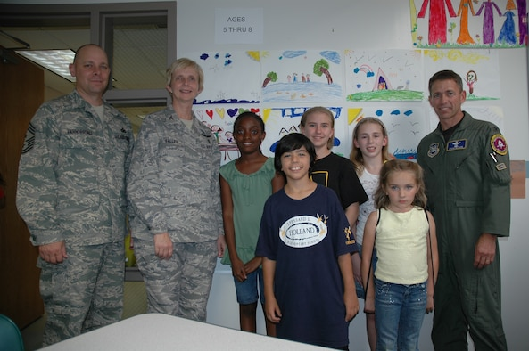 45th Space Wing Command Chief Master Sgt. Dennis Vannorsdall, 45th Medical Group Commander Col. Florence Valley and 45th Space Wing Vice Commander Col. Stephen Butler with some of the participants of the Poster Contest at the Youth Center March 28. (U.S. Air Force photo by Airman 1st Class David Dobrydney)