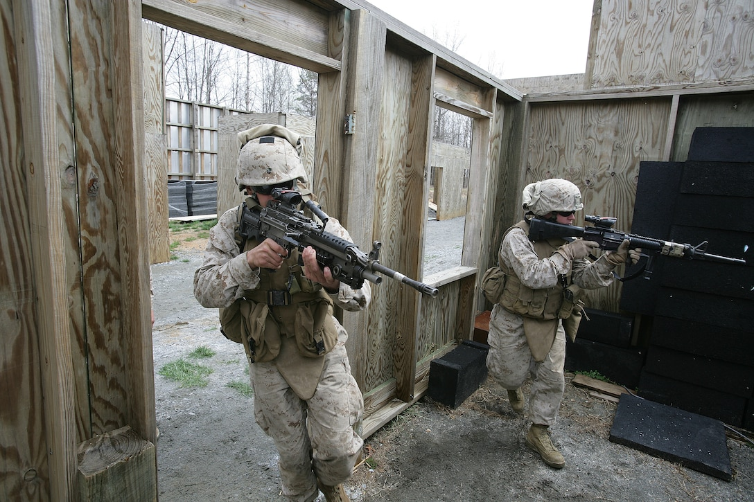 Lance Cpl. Joseph Lourenco and Pfc. Daniel Bolsar clear a room during a portion of the urban assault course at Fort Pickett here today. The live-fire training was held to prepare Battalion Landing Team, 2nd Battalion, 6th Marine Regiment's Company E for their upcoming deployment this fall.