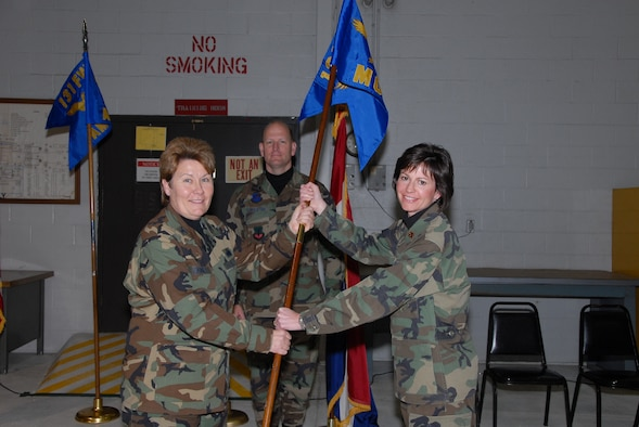 Colonel Terri Chaney accepts the 131st Maintenance Operations Squadron's guideon from its outgoing commander, Major Kimbra Halter.