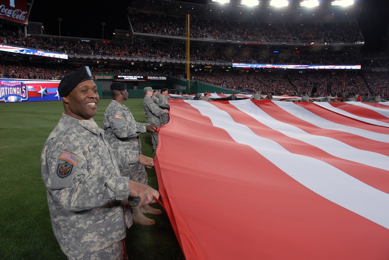 Maj. Bernard Napier, with the D.C. National Guard?s 74th Troop Command, holds one of two giant American flags unfurled on the outfield during pre-game ceremonies for the Inaugural Game at Nationals Park in Washington, D.C., on March 30, 2008. The D.C. Air National Guard's 121st Fighter Squadron also provided an F-16 Fighting Falcon flyover. (U.S. Army photo by Staff Sgt. Jim Greenhill) (Released)