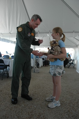 """Bailey Reese, Hero Hugs founder and president, """"coins"""" Col. Darryl Roberson, 325th Fighter Wing commander, during the 2008 Gulf Coast Salute for his military service."""