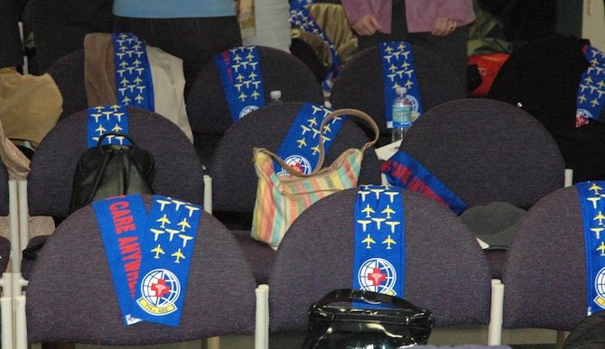 """MCGUIRE AIR FORCE BASE, N.J. -- 714th Aeromedical Evacuation Squadron scarves adorn the chairs of unit members during the squadron's deactivation ceremony on March 29.  Activated since October 1994, the Reserve members particpated in numerous worldwide missions. Their task of providing care to sick and injured shows credence to the unit slogan """"Patient Care Anywhere"""" as printed in bold red letters on the scarves..  (U.S. Air Force photo/Master Sgt. Chuck Kramer)"""