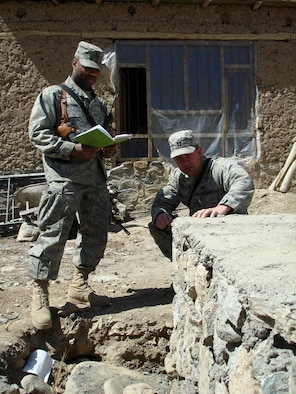 Capt. Jason M. Aftanas, Panjshir Provincial Reconstruction Team engineer, takes an initial look at a foundation for a schoolbook repository and passes along the information to his partner, Capt. Kenneth McGinnis at the site near the Khenj District Center April 1.  (U.S. Air Force photo by Capt. Jillian Torango)