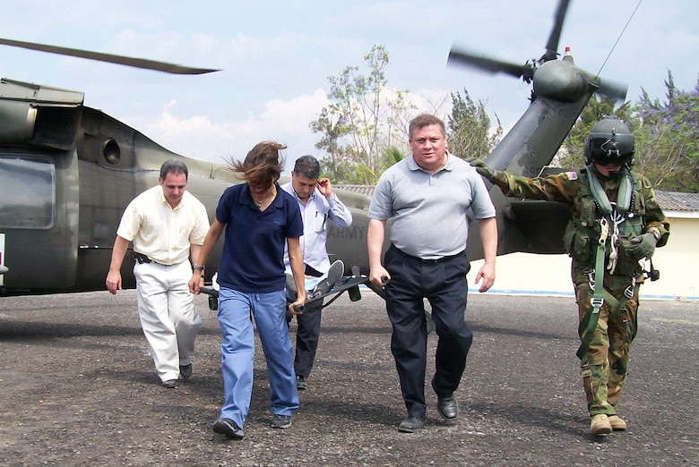SOTO CANO AIR BASE, Honduras-- Army flight medic Staff Sgt. Joseph McCormick leads Honduran medical professionals away from a Blackhawk helicopter during an information exchange at Hospital Militar Luis Alonso Discua. One aspect of the exchange was familiarization with practicing safe delivery and recovery of patients to a running JTF-Bravo MEDEVAC helicopter.