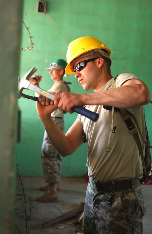 LAS MESAS, Honduras - Sgt. Juan M. Ozuna from the 672nd Engineer Company repairs a dilapidated schoolhouse during their Annual Training. U.S. Army engineers are among the personnel participating in Beyond the Horizon, a training exercise that provides infrastructure renovation, as well as basic medical and dental care, to rural areas of this Central American country. Soldiers working in Las Mesas will replace the school's doors and windows, repair the roof, and repaint the entire structure, in addition to improving a soccer field on which local children play. (Photo by Sgt. Claude W. Flowers, 304th Public Affairs Detachment.)
