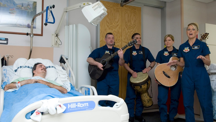 Members of the Air Force Heartland of America Band's Night Wing perform for a servicemember April 5 at the James A. Haley Veterans' Hospital in Tampa, Fla. The band performed throughout the hospital to lift the spirits of military members.  Night Wing is an ensemble of the Heartland of America Band stationed at Offutt Air Force Base, Neb. (U.S. Air Force photo/Staff Sgt. Bennie J. Davis III)