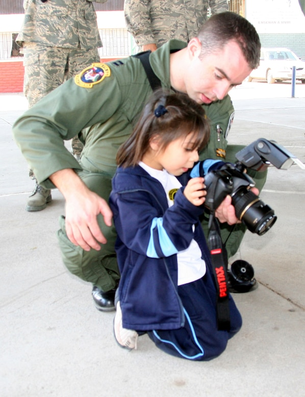 SANTIAGO, Chile - Capt. John Peltier, 391st Fighter Squadron, teaches a Chilean orphan how to take pictures during a performance of the Air Force Band of the Central States at Koinomadelfia Orphanage west of Santiago April 3. Twenty Airmen participating in the FIDAE airshow took a break from aircraft displays and demonstrations to visit more than 30 preschool-aged children at the orphanage to hand out toys, patches and stickers. Koinomadelfia is home to 80 children who have been rescued from domestic violence situations. The FIDAE air show hosts aircraft from 42 countries and is the largest event of its kind in South America. (U.S. Air Force photo by/ 1st Lt. Candace Cutrufo)