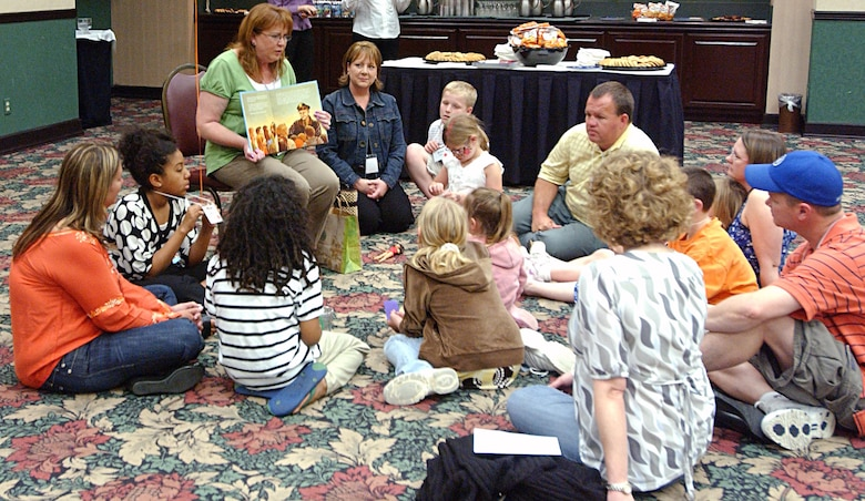 """Children – and a few parents -- listen to an adult volunteer read """"Mercedes and the Chocolate Pilot"""" during the Tell Me a Story™ event sponsored by the Texas Military Forces State Family Program in Austin March 29. (Texas Military Forces photo by Sgt. Ann Benson)"""