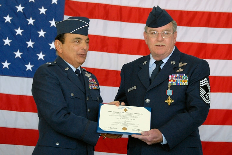 Retired Brig. Gen. Frank Cardile (left) awards retired Chief Master Sgt. Dennis Richardson after presenting him with the Air Force Cross April 5 at the Francis S. Gabreski Airport in New York. Chief Richardson was awarded the Air Force's second-highest honor for valor because of his actions during a March 1968 mission to rescue Airmen in Vietnam. During the mission, Richardson stood exposed in the door of an HH-53 Jolly Green Giant helicopter to fight off enemy forces attempting to board it. (U.S. Air Force photo/Staff Sgt. David J. Murphy)