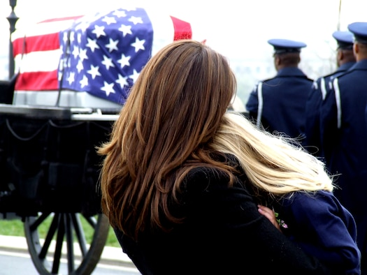 Family members of former missing in action Airman, Maj. Robert F. Woods, watch as the cason carrying him is prepared to move to a grave site April 9, 2008, at Arlington National Cemetery, Va.  On Nov. 30, 2007, the Air Force announced that Major Woods, along with co-pilot Capt. Johnnie C. Cornelius, were identified and their remains returned to the United States from Vietnam.  On June 26, 1968, Major Woods and Captain Cornelius were flying a visual reconaissance mission over Quang Binh Province, Vietnam, when their O-2A Skymaster aircraft crashed in a remote mountainous area.  Major Woods was buried with full military honors nearly 40 years after he disappeared in the crash.  (U.S. Air Force Photo/Tech. Sgt. Scott T. Sturkol)