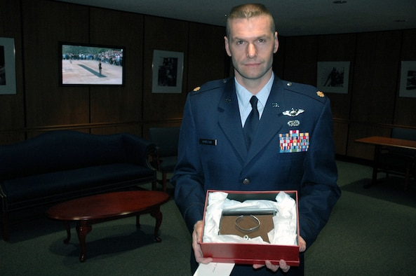Maj. Phil Heseltine, U.S. Air Force Expeditionary Center executive officer to the commander, Fort Dix, N.J., shows the POW/MIA bracelet he wore for 18 years.  Major Heseltine presented the bracelet to the family of Maj. Robert F. Woods, whose name is on the bracelet, during the funeral for Major Woods at Arlington National Cemetery April 9, 2008.  (U.S. Air Force Photo/Tech. Sgt. Scott T. Sturkol)