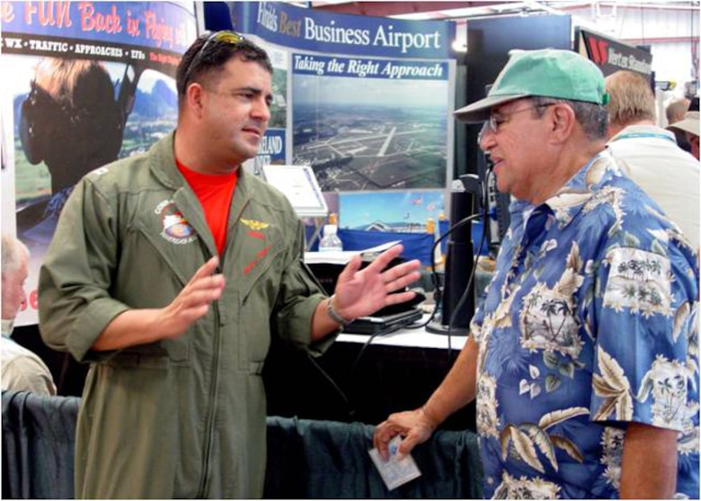 USN Lieutenant Hector Zayas discusses airspace issues with a foreign pilot attending Sun ?n Fun 2008.  The Continental U.S. NORAD Region (CONR) has expanded its public outreach team to include multilingual aviators capable of connecting with foreign pilots on topics of air defense and flight restricted zones.  (U.S. Air Force photo)