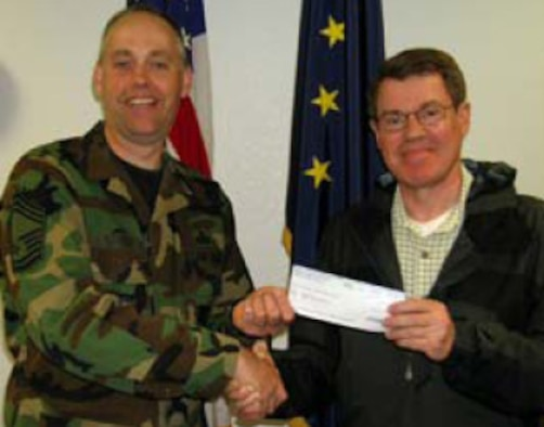 Alaska USA's Military Operations Branch Manager, Carl Bradford, shown here presenting CMSgt. David Streit a $500 check in support of this year's Family Day. Photo by SSgt. Eric Hamilton, 176 WG/PA.