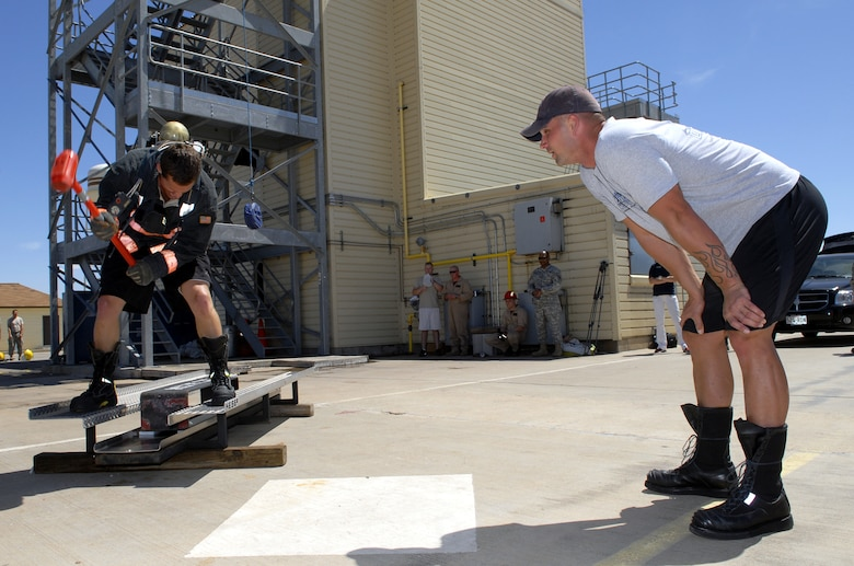 Andy Scholes, KLST San Angelo sportscaster, tries to move 150 pounds with a sledge hammer during the forceable entry simulation part of the course while Marine Staff Sgt. Nicholas Cook, SAM Squad team member, shouts words of encouragement. (U.S. Air Force photo by Senior Airman Kamaile Chan)
