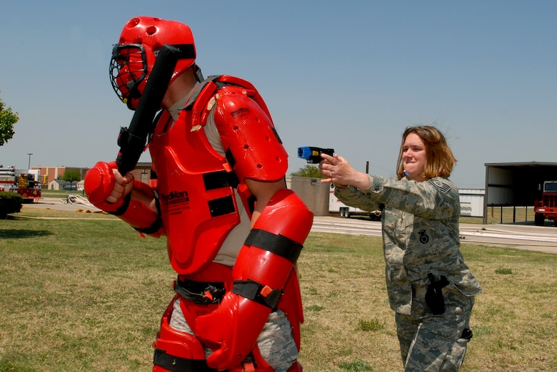 Technical Sergeant Rachel Taylor prepares to deploy her Taser on a red-suited Airman 1st Class Charles Bird during Taser training Tuesday. (U.S. Air Force photos by Tech. Sgt. Gina O'Bryan)