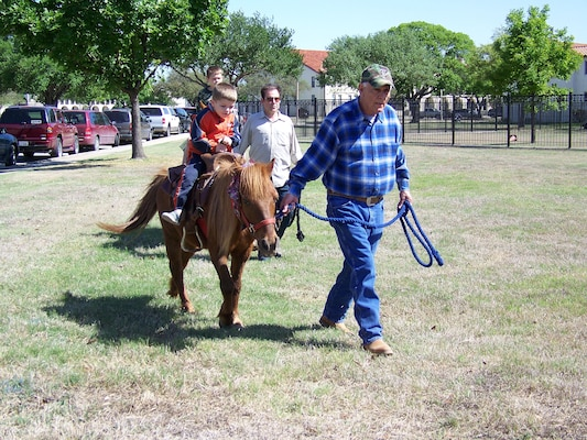 Patrick Hammond enjoys a pony ride with the help of wrangler Jim Wasaff. (Photo by Maggie Armstrong)