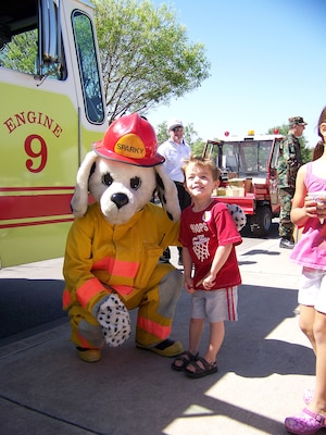 Trey Coalson says hello to Sparky, the base fire department mascot. (Photo by Maggie Armstrong)