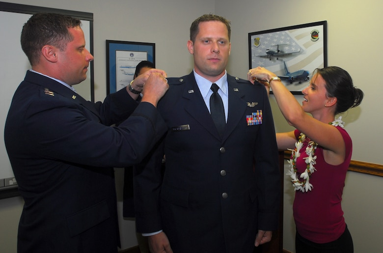 Maj. (sel) Dennis Birchenough (left), Air Force Institute of Technology and Mary Birchenough (right) pin the rank of Major on Peter Birchenough, 65th Airlift Squadron, during a promotion ceremony here. The newly promoted majors are identical twin brothers. U.S. Air Force Photo/Staff Sgt. Erin Smith