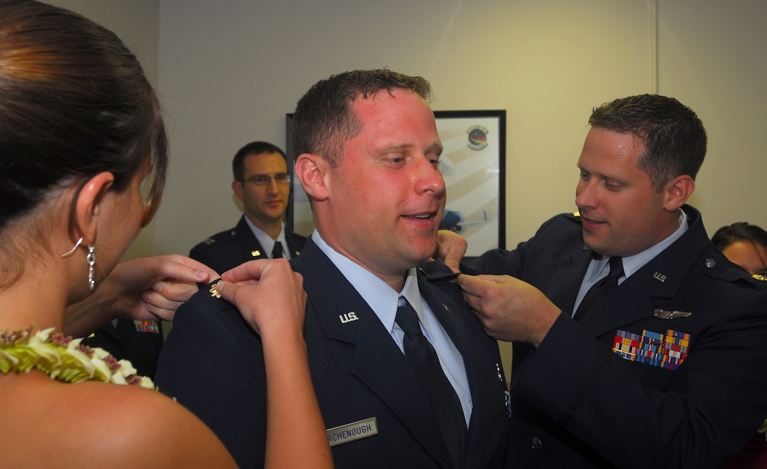 MacKenzie Collatz (left) and newly promoted Maj. Peter Birchenough (right), 65th Airlift Squadron pin the rank of Major on Dennis Birchenough, Air Force Institute of Technology, during a promotion ceremony at the 65th Airlift Squadron conference room.  The majors are identical twins who were promoted to Major on the same day.