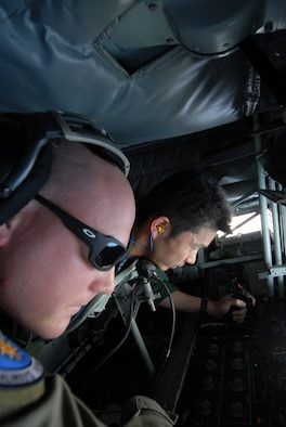 Senior Airman Christopher Pedersen, 909th Air Refueling Squadron, explains to Shinichi Kudoh, Japan Air Self Defense Force, the procedures for operating the boom during refueling training at Kadena Air Base, Japan. The training was conducted to familiarize JASDF members with U.S. Air Force refueling procedures. (U.S.photo/Staff Sergeant Darnell T. Cannady)